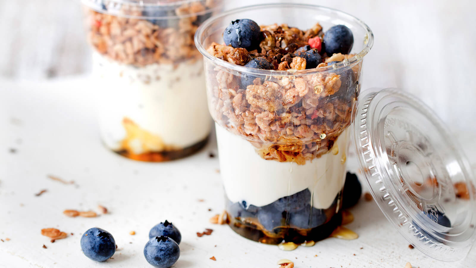 Granola with blueberrys and crème fraiche in a plastic cup