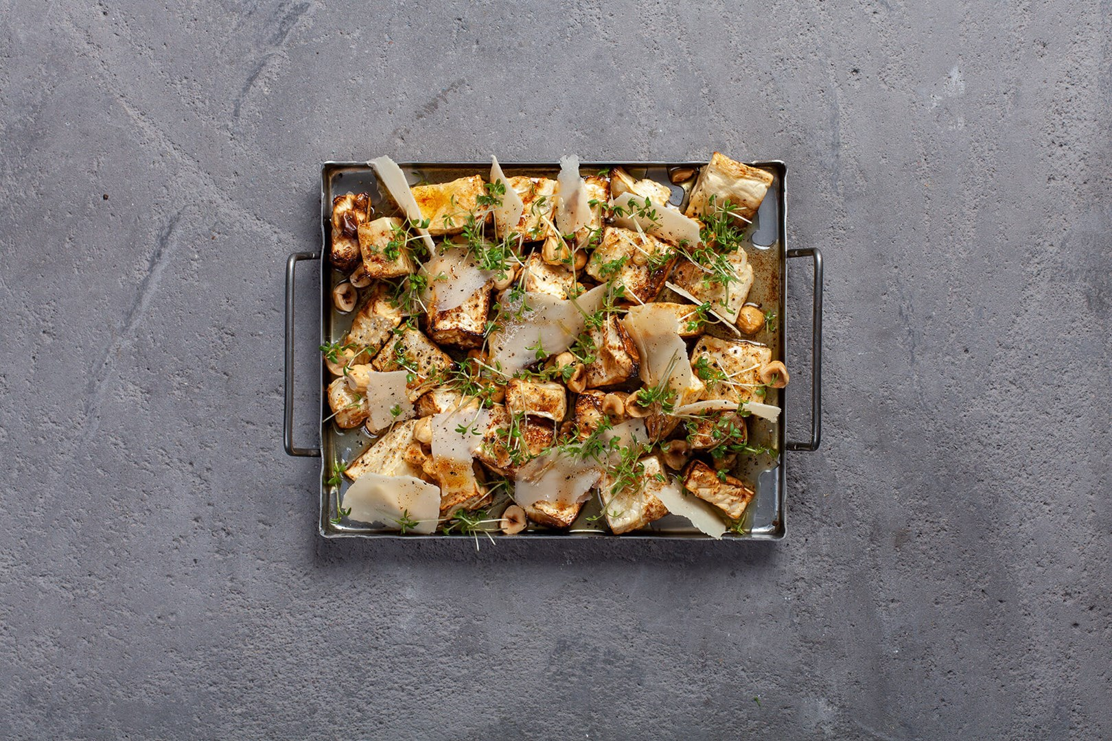 Small oven tray with roasted celeriac topped with parmesan and hazel nuts