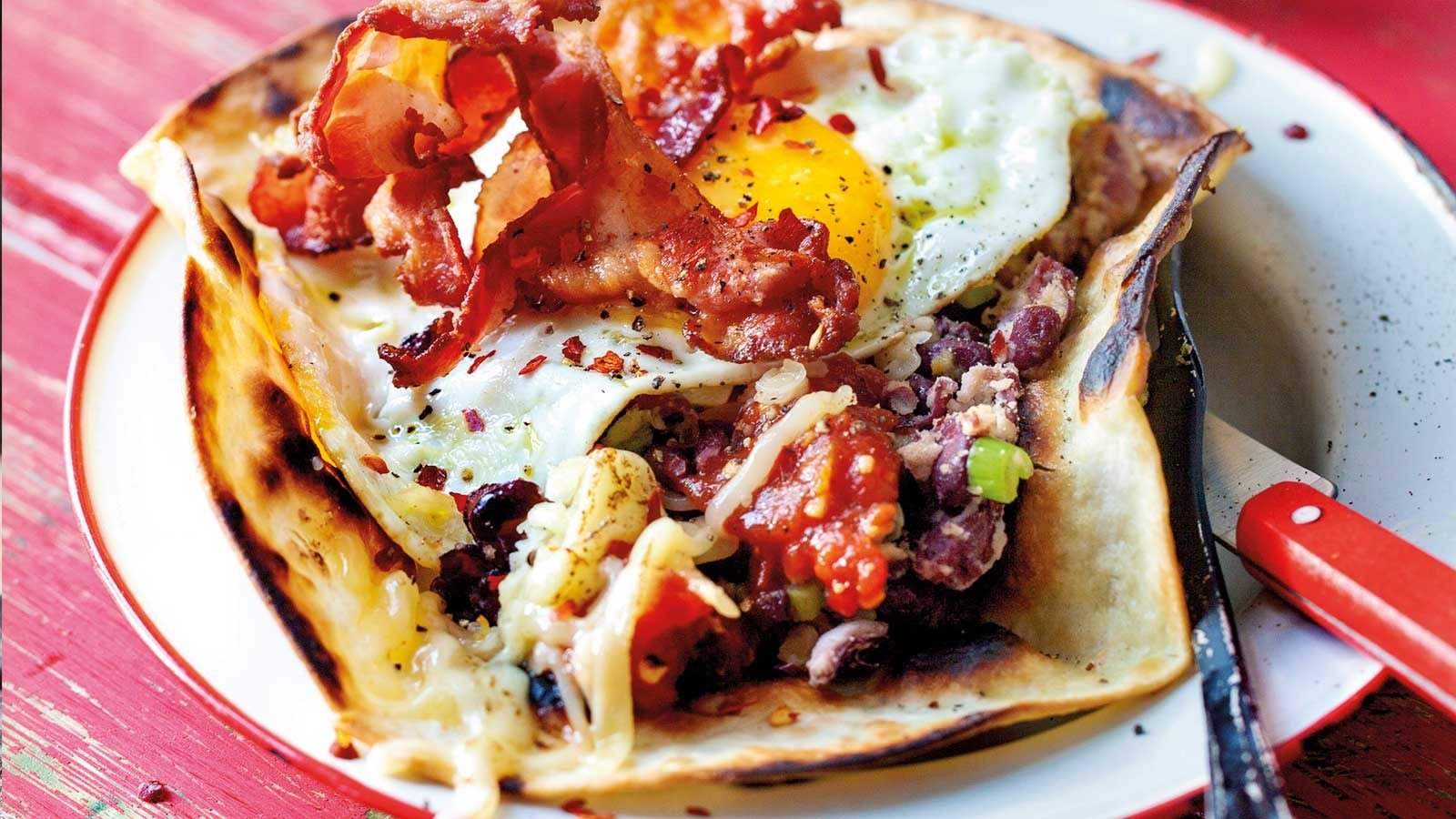 Open breakfast tortilla with fried eggs, grilled tomatoes, salsa and baked beans