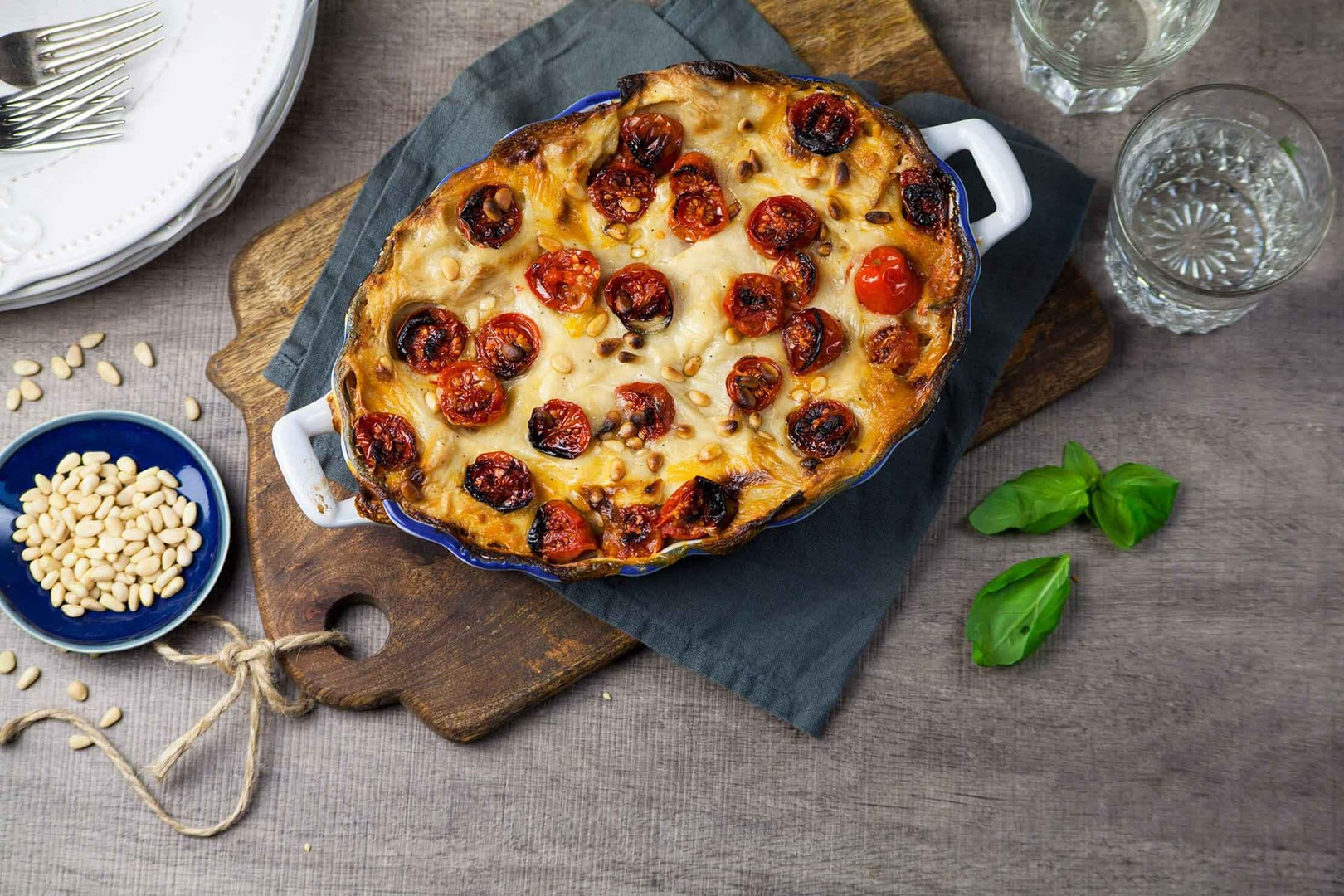 Vegan lasagne with cherry tomatoes in an ovenproof dish