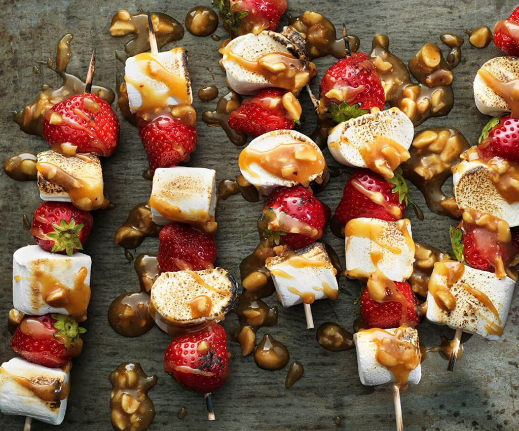 Skewers with strawberries and marshmallows drizzled with caramel sauce