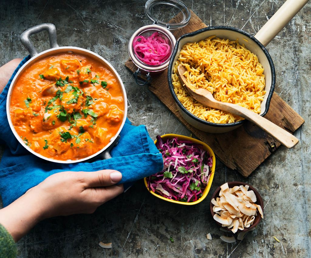 Hands holding a saucepan with creamy coconut chicken