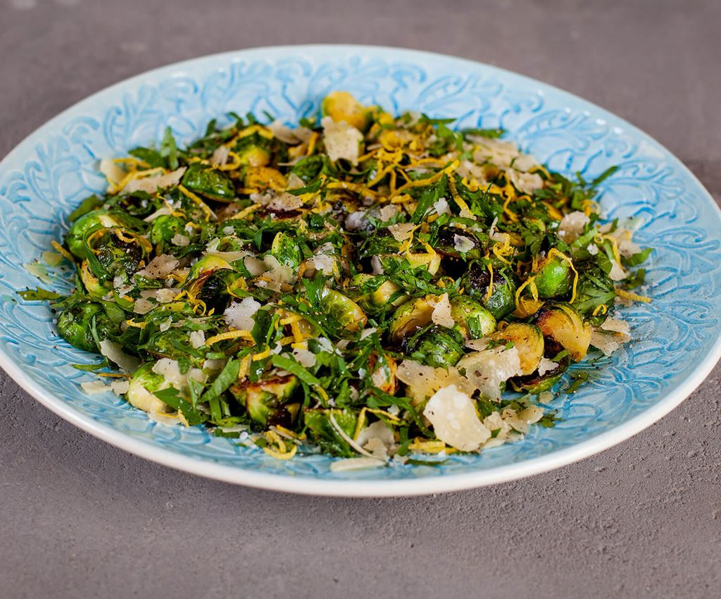 Fried brussels sprouts with gremolata and parmesan on a blue serving dish