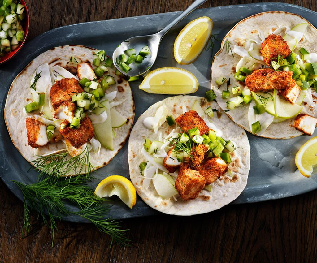 Three fish tacos served on a tray