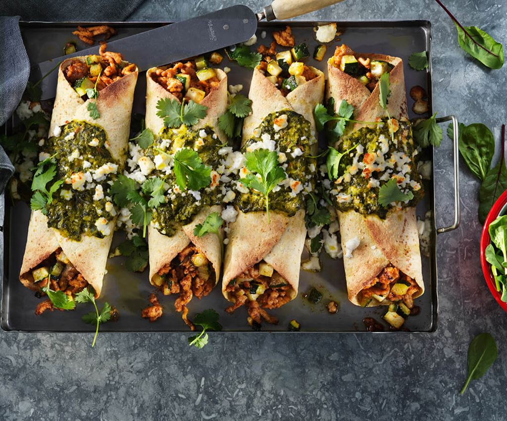 Four spinach and chicken enchiladas on a tray