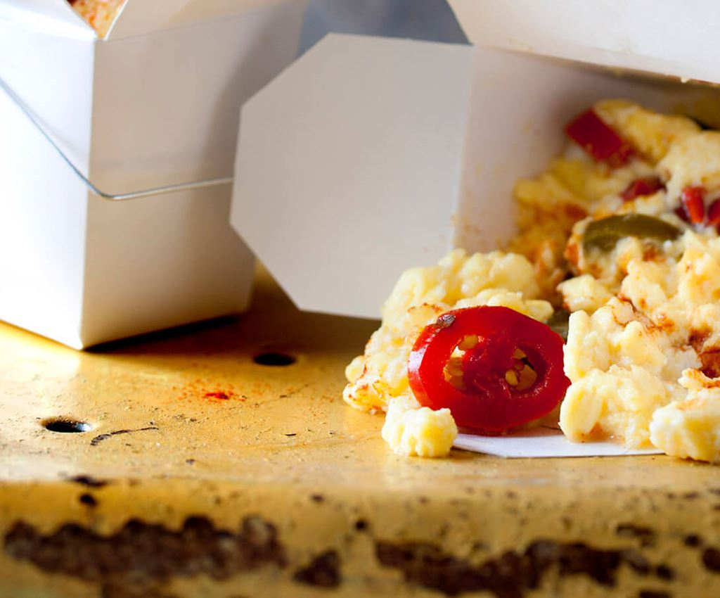 Scrambled eggs with jalapeño in take away boxes