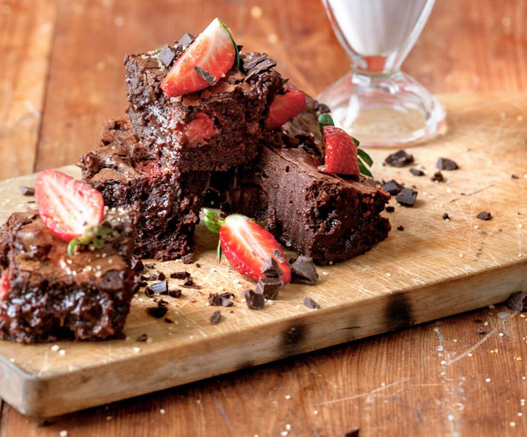 Chocolate brownies with straberries on a wooden board
