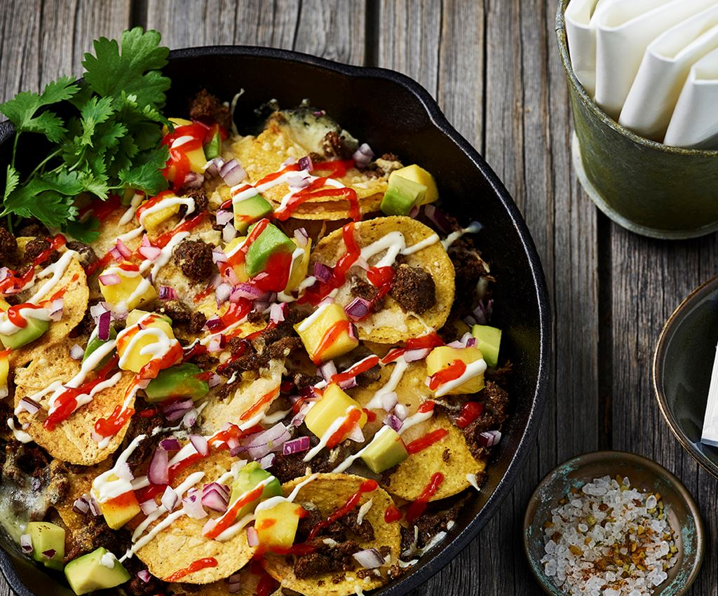 Nacho plate met loaded nachos met  Jamaican Jerk pulled oats en mango