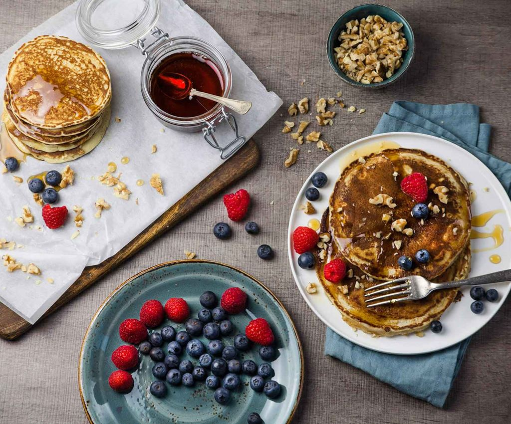 Vegan pancakes with raspberries, blueberries, maple syrup and pecans