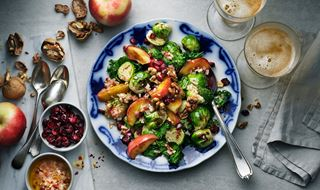 Salad with brussels sprouts, kale, apple and walnuts on a large plate