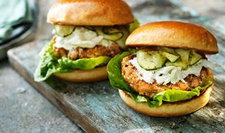 Two salmon burgers in bread with pickled cucumber and fennel salad
