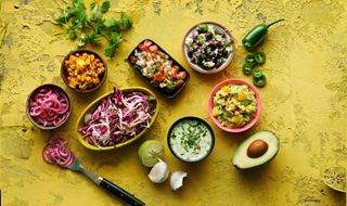 Seven bowls with different side dishes to Latin American food
