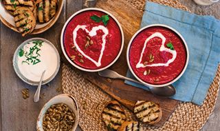 Two bowls of beetroot soup garnished with a heart of garlic yoghurt. Served with garlic bread