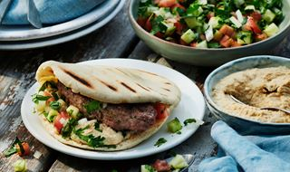 Shish kebab in pita with hummus & chopped tomato & cucumber salad