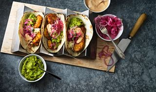 Three tacos with corn fritters and guacamole